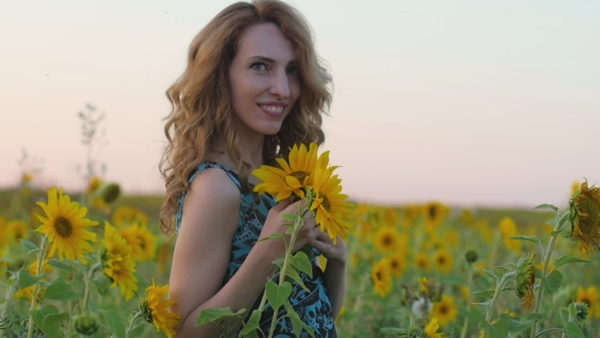 Portrait of a young attractive woman with red hair and a blue dress in a field of sunflowers at sunset. Beautiful model against the backdrop of the setting rays of the sun | Shutterstock HD Video #1071017176
