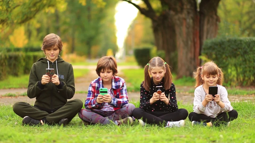 Happy children friend girls group sit with cross legs on grass and playing internet game with mobile smartphone. kids texting message on smartphone outdoor in summer garden. Blogger lifestyle | Shutterstock HD Video #1071017209