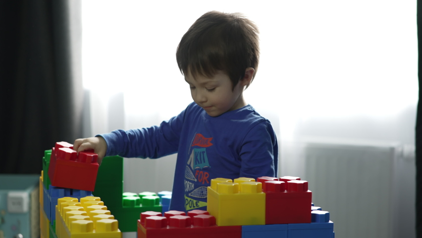 The boy is playing an educational game of dice in the nursery. The child collects the cubes and stacks them one on top of the other. Colorful dices educational game for kids.   Shutterstock HD Video #1071017413
