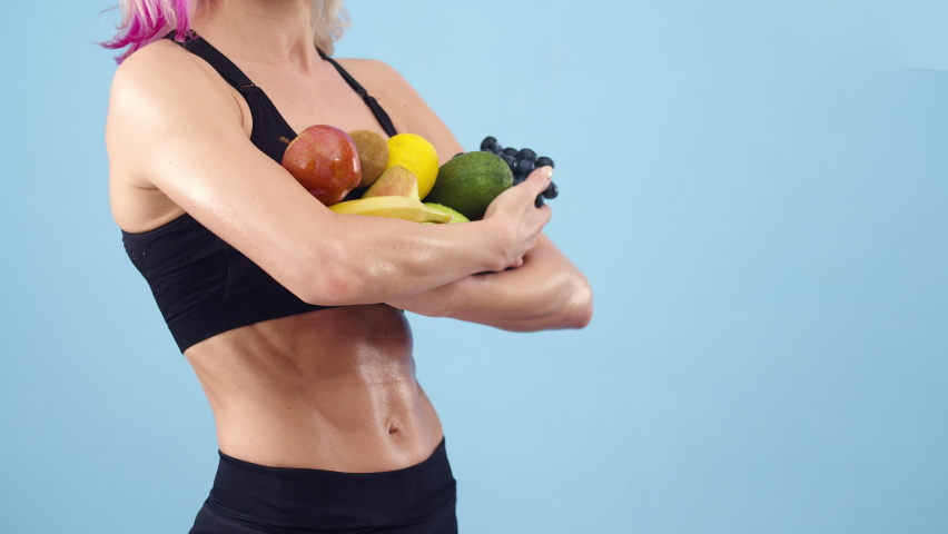 Sports woman holds a lot of fruit in hands the studio, close up. Woman with an muscular belly holds fruit with hands, a blue background. Concept of healthy eating and sports lifestyle. | Shutterstock HD Video #1071017788