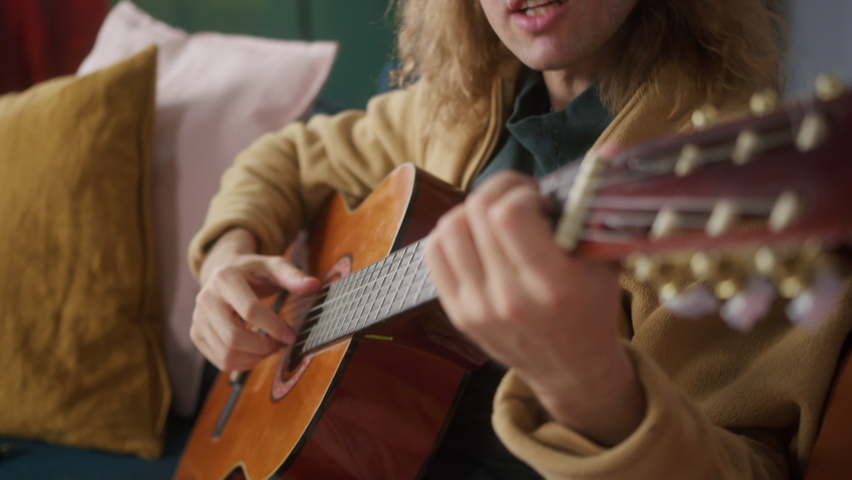 Man playing acoustic guitar. Tutorial with smartphone. Blogger Teacher teaching how to play on music instrument. Mobile screen recording online music video at home.   Shutterstock HD Video #1071018442