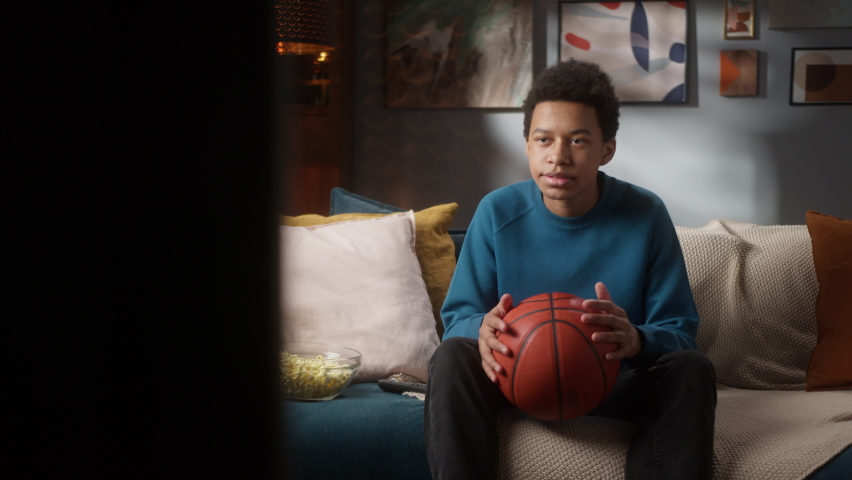Serious black man teenager holding basketball ball and sitting on sofa watching professional game on tv in living room, young teen athlete, sport portrait at home, high school kid rooting for team.  | Shutterstock HD Video #1071018454