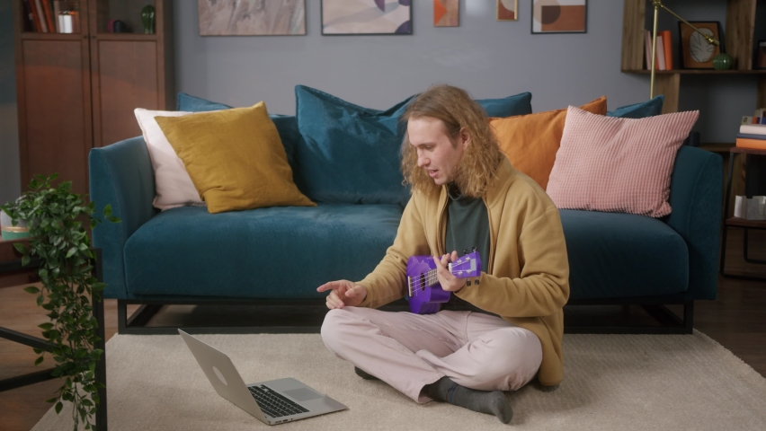 Happy man using laptop computer playing purple ukulele sitting on floor. Blogger Teacher teaching how to play on music instrument online. Remote musical learning.    Shutterstock HD Video #1071018472