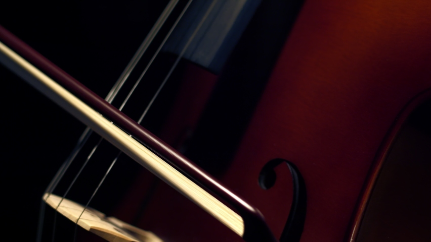 On strings of cello play with bow in darkness, close-up. On a string musical instrument the violoncello musician plays with bow. Concept learning to play the cello.   Shutterstock HD Video #1071019528