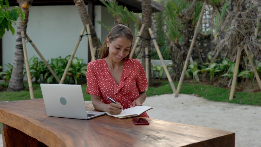 Happy digital nomad writing notes about freelance project using personal planner outdoors, smiling copywriter or blogger creating text publication sitting at table with netbook    Shutterstock HD Video #1071021124