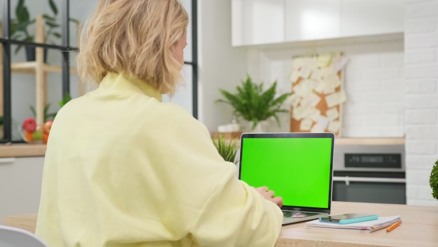Girl uses green screen chroma key laptop for learning, writes down useful information. distance learning, e-education, e-learning, homeschooling concept. close-up over shoulder POV. | Shutterstock HD Video #1071021808
