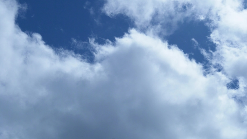 The Wind Drives White Gray Cumulus Puffy Clouds in the Blue Sky. Time Lapse of Flying Clouds in the Blue Sky. Covering The Sky With Clouds. Cloud Cover, Air, Atmosphere, Nature, Windy Weather.