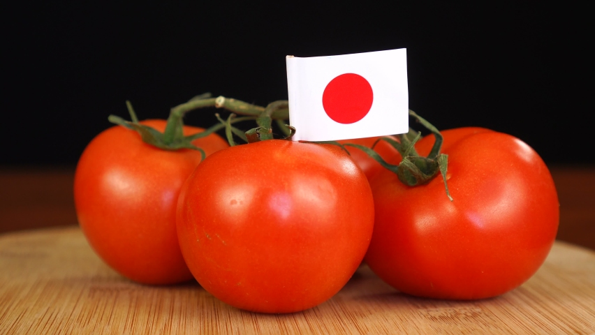 Man placing decorative toothpick with flag of Japan into bunch of tomatoes. | Shutterstock HD Video #1071128866