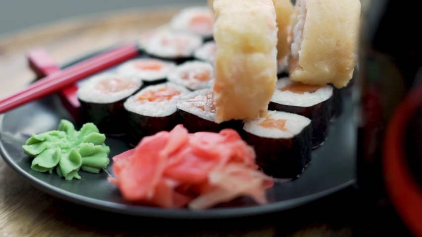 Dinner of Freshly Made Sushi Rolls with Ginger Horseradish Red Chopsticks and Soy Sauce, Close-up. A Japanese Dish, A Healthy Asian Food made of Seafood and Rice. Japanese Restaurant. | Shutterstock HD Video #1071129949