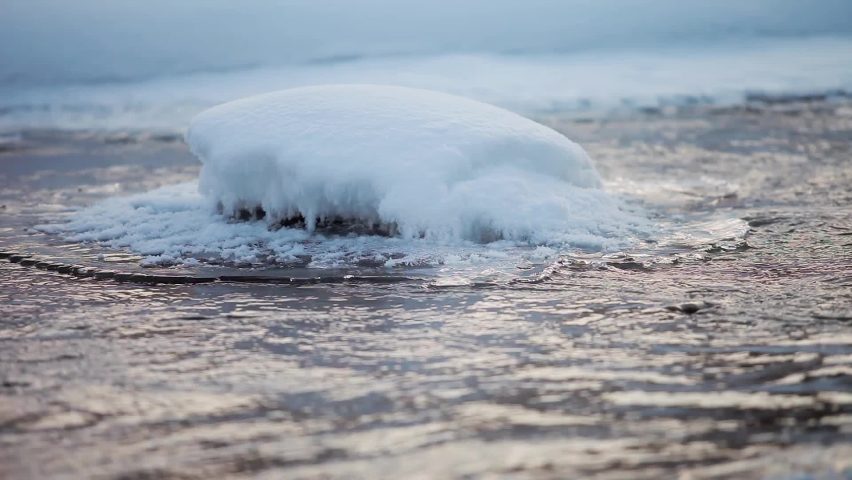 Right in the center of the descending stream, a snow island has appeared that resists the movement of the water.   Shutterstock HD Video #1071138124