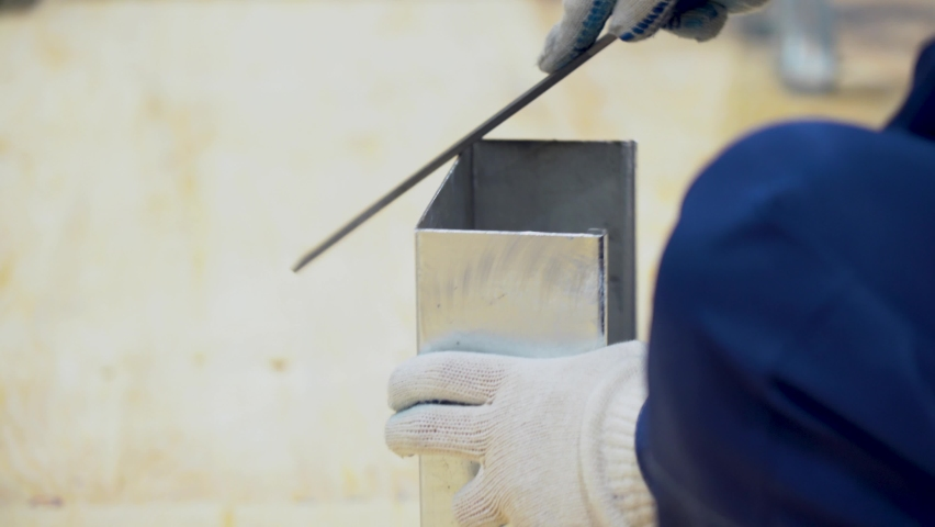Employee man wear blue suit, protective white gloves, uses a file, aligns, grinds sharp edges of tin metal gutter against a blurry light background. Close up view of male worker hands with tool.   Shutterstock HD Video #1071138217