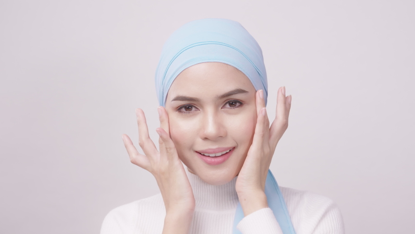 Close up of young beautiful muslim woman with hijab isolated on white background studio, muslim beauty skin care concept.   Shutterstock HD Video #1071138517