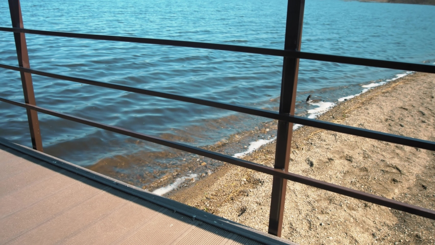 The camera zooms in on the iron fence, through which you can see the sand and the lake.   Shutterstock HD Video #1071138646
