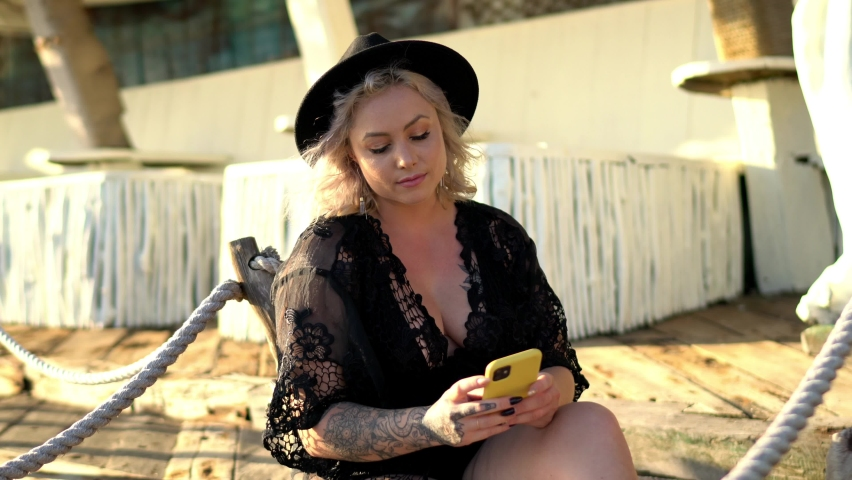 Caucasian female blogger enjoying smartphone browsing via cellphone application, millennial woman in trendy hat using mobile application for web phoning and network chatting | Shutterstock HD Video #1071138688