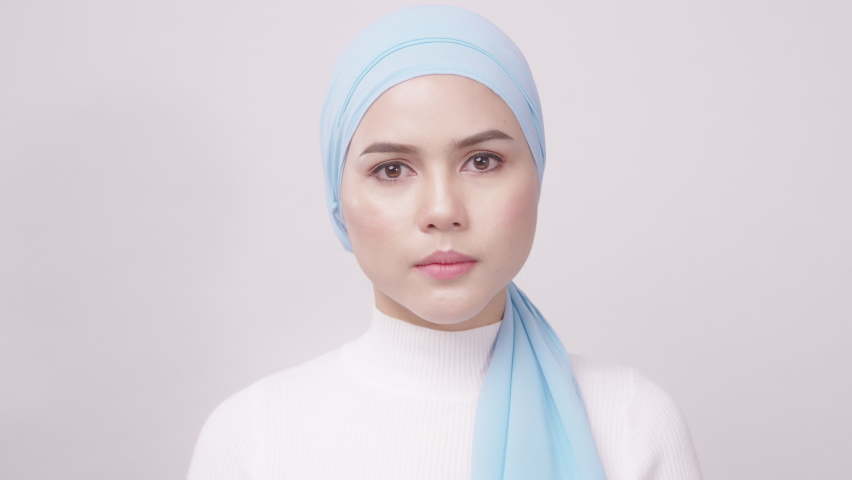 Close up of young beautiful muslim woman with hijab isolated on white background studio, muslim beauty skin care concept. | Shutterstock HD Video #1071139321