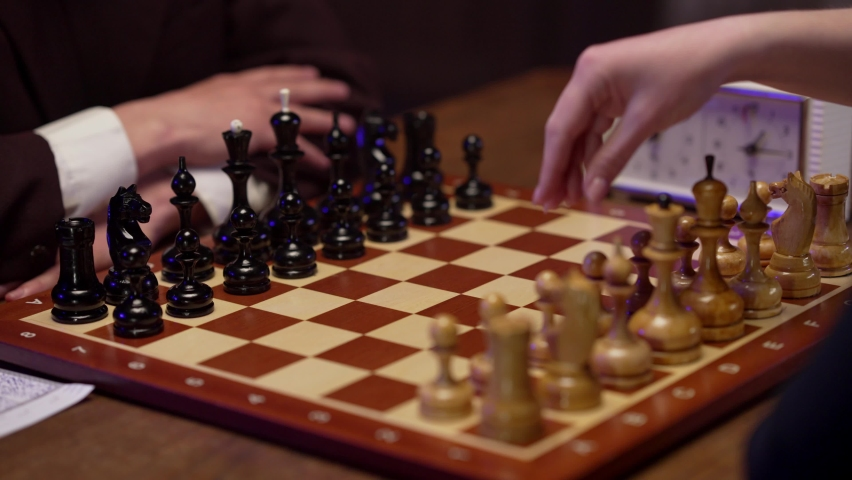 Two chess players man and woman play chess. Debut Accepted Queen's Gambit, King's Gambit, Philidor's Defense. Cinematic filming of a chess game. Antique chess board. | Shutterstock HD Video #1071139576