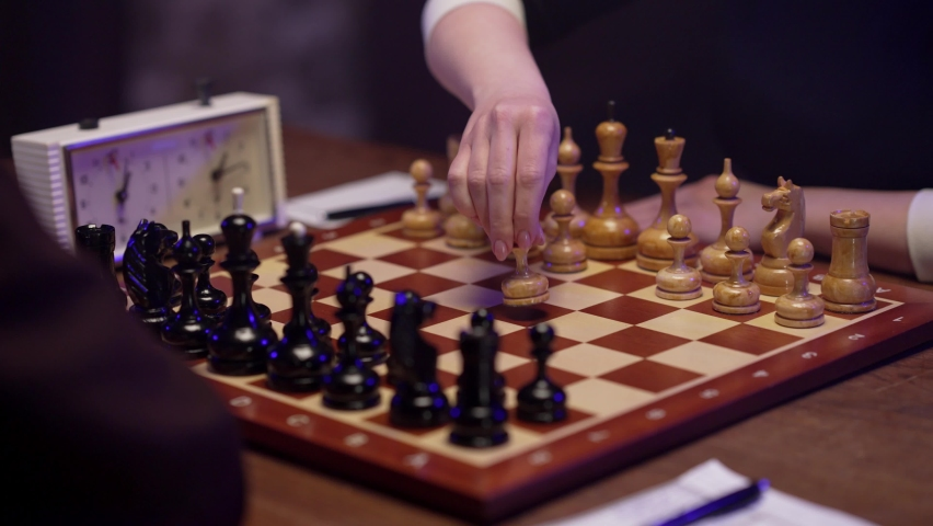Two chess players man and woman play chess. Debut Accepted Queen's Gambit, King's Gambit, Philidor's Defense. Cinematic filming of a chess game. Antique chess board. | Shutterstock HD Video #1071139594