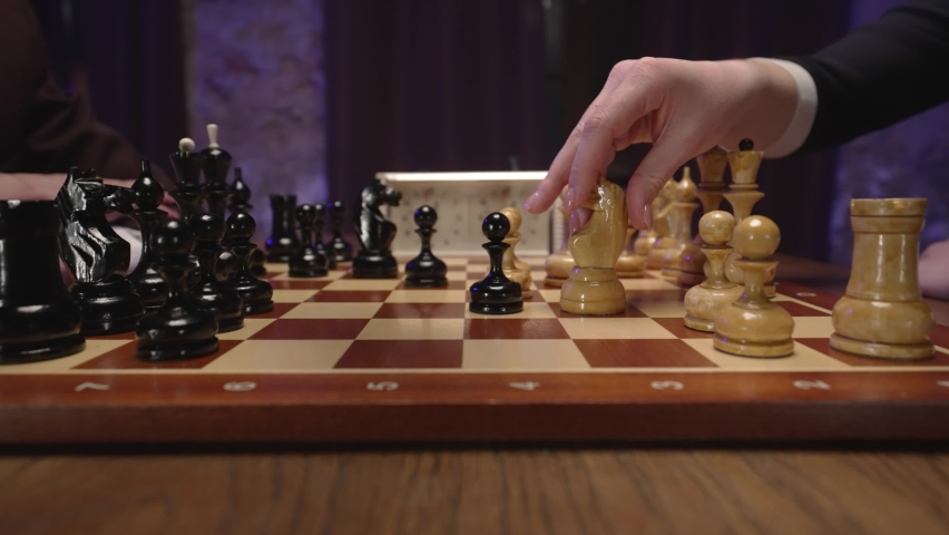 Two chess players man and woman play chess. Debut Accepted Queen's Gambit, King's Gambit, Philidor's Defense. Cinematic filming of a chess game. Antique chess board. | Shutterstock HD Video #1071139600