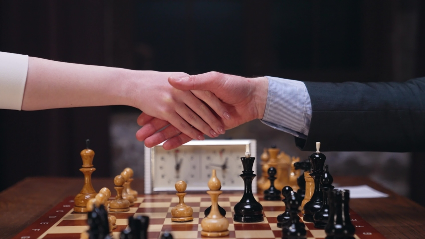 Two chess players man and woman play chess. Debut Accepted Queen's Gambit, King's Gambit, Philidor's Defense. Cinematic filming of a chess game. Antique chess board. | Shutterstock HD Video #1071139630