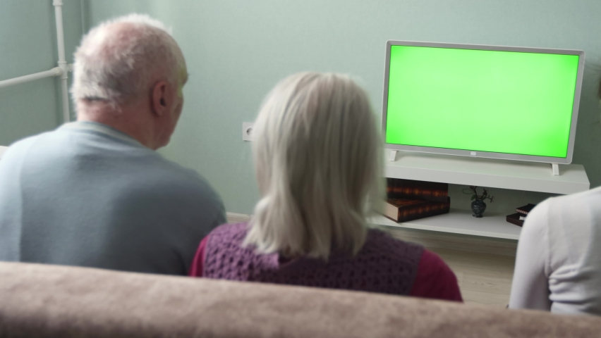 Family watching TV. Green screen.Two couples, an elderly and a middle-aged couple, are sitting on the couch at home. In front of them is a green screen TV. Horizontal panning. | Shutterstock HD Video #1071139666