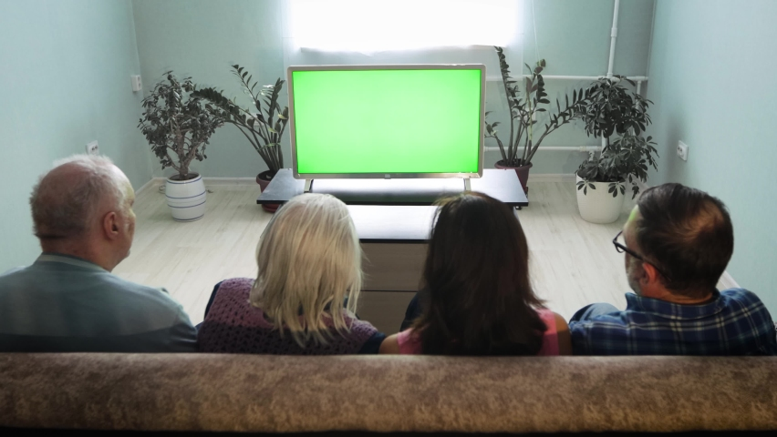 Family watching TV. Green screen. A family of two generations is sitting on the couch at home. In front of them is a green screen TV.  | Shutterstock HD Video #1071139669