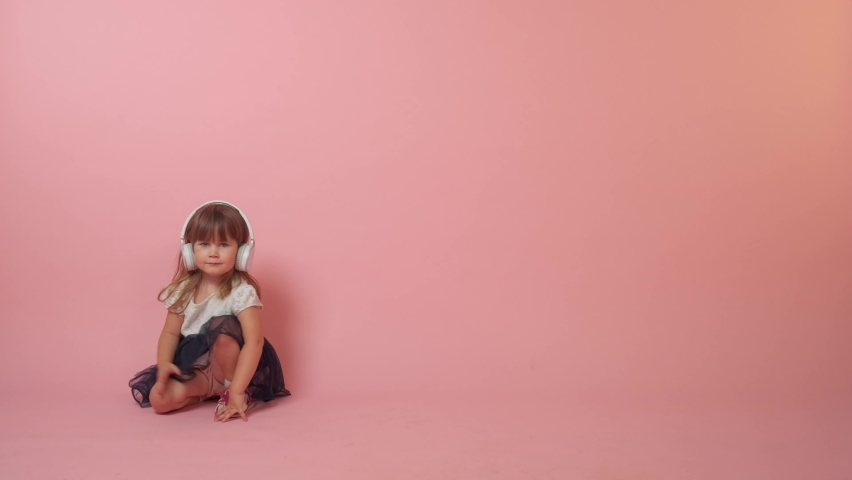 Cute little girl jumping, hears music. I dropped my headphones to the floor. Beautiful bright festive outfit. Copy space to the right. Pink background. | Shutterstock HD Video #1071142309