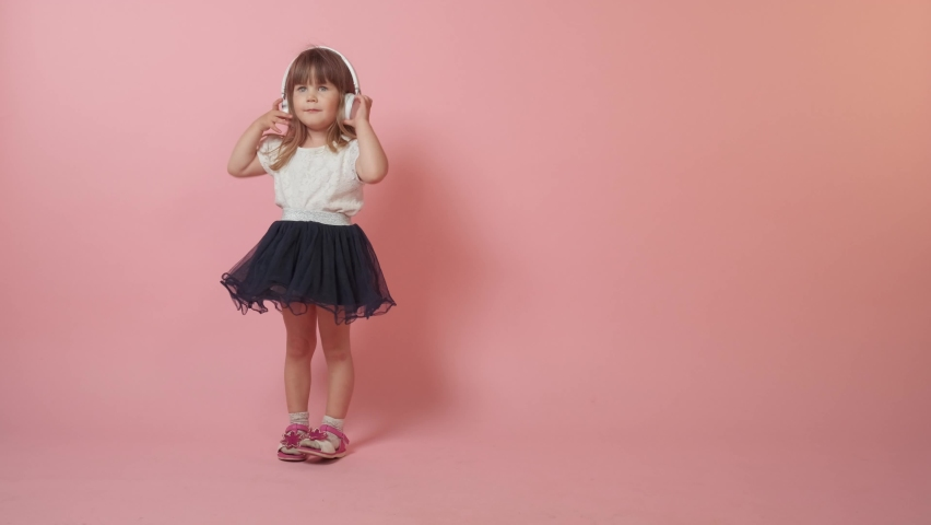 Cute little girl hears music while standing, enjoying, relaxing. Beautiful bright festive outfit. Copy space to the right. Pink background. | Shutterstock HD Video #1071142336