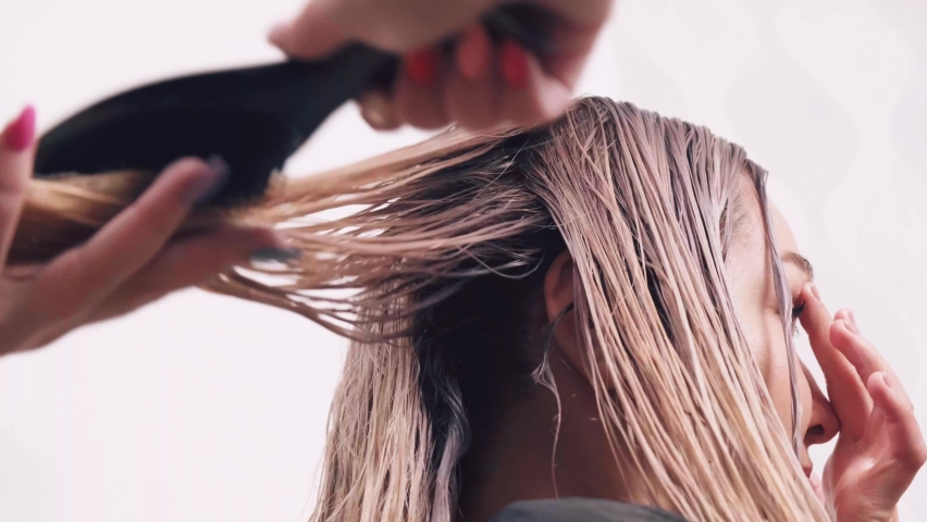 Professional hair care. Hairdresser combing wet hair in a beauty salon. Beautiful long blonde hair. | Shutterstock HD Video #1071142363