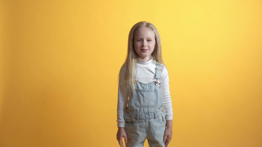 Beautiful cute girl schoolgirl looks at the camera with a surprised face. Yellow background. | Shutterstock HD Video #1071142399