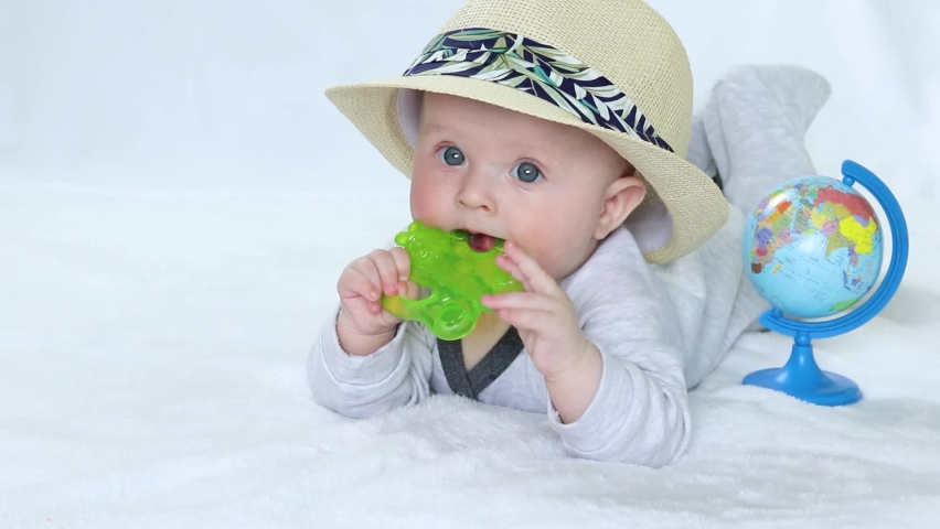 Baby in a hat with a toy and a globe.Copy space - concept of safe travel, tourism, vacation, dream of the beach, family vacation at sea, flight, trip, travel abroad, sunny and hot day, summer, warmth | Shutterstock HD Video #1071142897