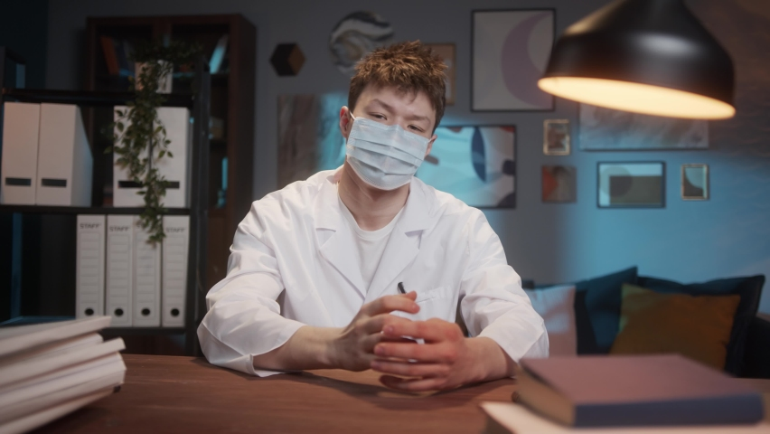 COVID-19 Coronavirus pandemic, Asian doctor wearing surgical mask using video chat conference call, talking with patient, showing something on hand, gesturing. Consultation and learning online. | Shutterstock HD Video #1071142933