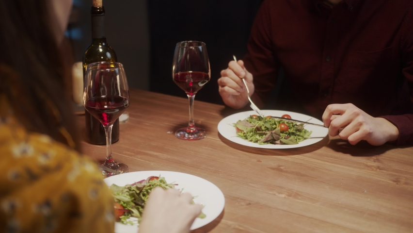 Engagement, man proposal marriage and gift a ring. Young Couple in love dinner, drinking red wine, cozy Saint Valentines Day celebration at home or in restaurant | Shutterstock HD Video #1071142957