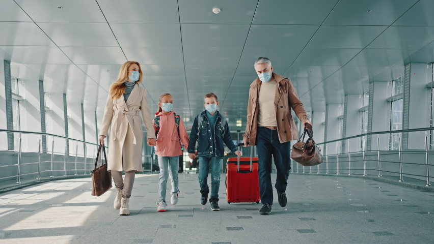 Family vacation. Mother and father holding hands of their children and walking down the airport corridor to flight, everyone wearing protective medical masks, slow motion Royalty-Free Stock Footage #1071165799