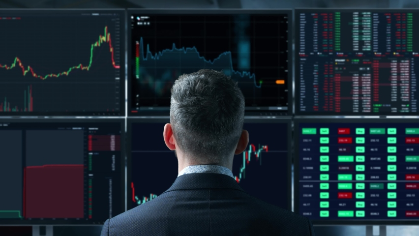 Trader is working with multiple computer screens full of charts and data analysis and stock broker trading online. Back view. Concept of bitcoin and stock market trading. Royalty-Free Stock Footage #1071207661