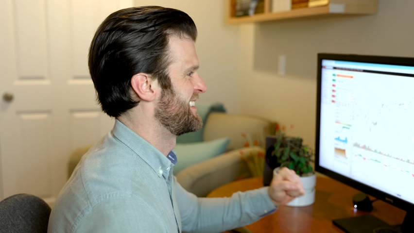 Man looking at finance chart on computer cheering, finished work project or other success working from home desktop computer. 4K 24FPS