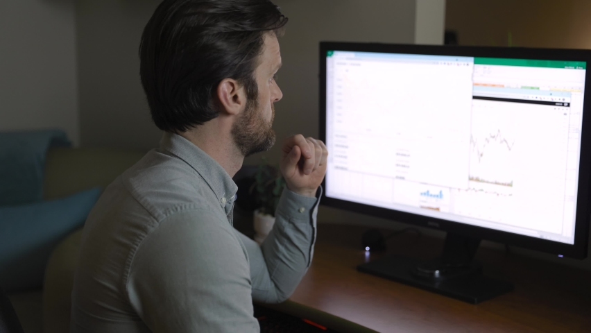 Man looking at finance chart on computer. 4K 24FPS