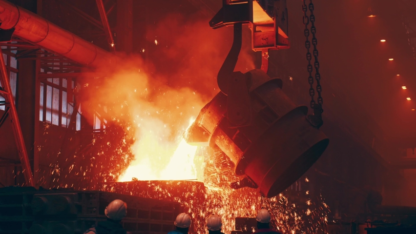 Pouring bright hot liquid steel or metal from ladle in blast furnace foundry metallurgical factory. Steel mill iron smelting process with bright sparks and smoke Royalty-Free Stock Footage #1071260212