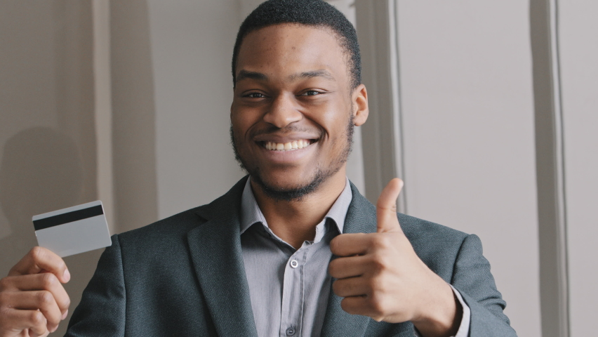 Portrait happy smiling handsome young african american bank employee businessman holding credit card showing thumb-up demonstrates the advantages of bank card. E-banking app service concept.  Royalty-Free Stock Footage #1071262885