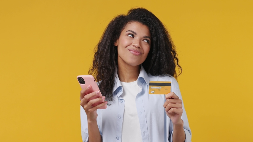 Young african woman in blue white t shirt use mobile cell phone hold in hand credit bank card doing online shopping order delivery to home booking tour isolated on yellow color wall background studio Royalty-Free Stock Footage #1071269581