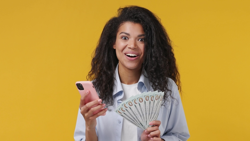 Excited joyful young african woman curly hair 20s years old wears blue white t shirt using mobile cell phone hold fan of cash money in dollar banknotes isolated on yellow color wall background studio Royalty-Free Stock Footage #1071269590