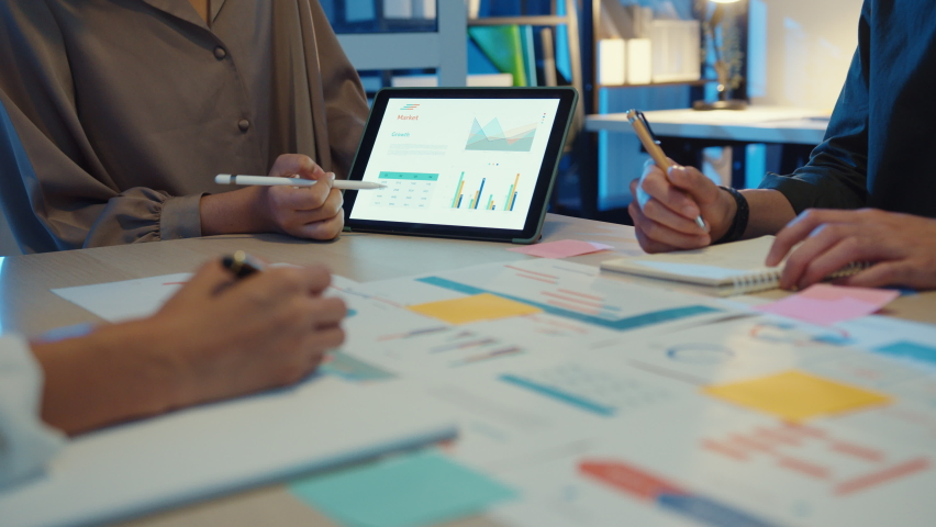 Close-up asia business people meeting plan analysis statistics brainstorm and header of team hold tablet pointing graph chart and employee take note. Finance strategy statistics success concept.