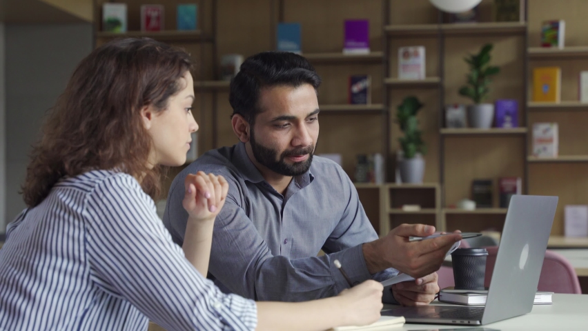 Professional indian teacher, manager or mentor helping latin student, new employee, teaching intern, explaining online job using laptop computer, talking, having teamwork discussion in office. Royalty-Free Stock Footage #1071309505