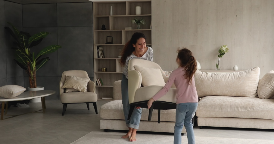 Woman and daughter rearranging furniture in spacious living room. Mom and kid move cozy armchair together, give high five enjoy weekend at new modern house. Happy homeowners family relocation concept