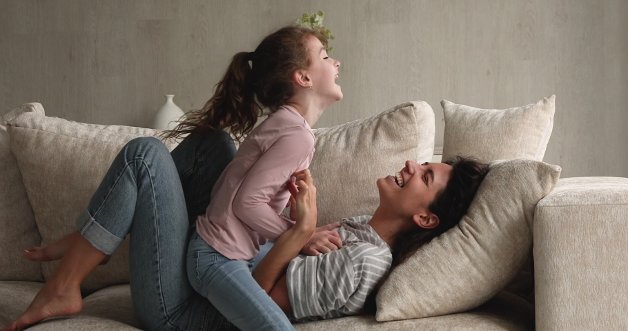 Latina mother caucasian daughter diverse family play funny active game on sofa in living room, loving parent tickling adopted kid girl express caress, bonding and love. Fun and leisure at home concept