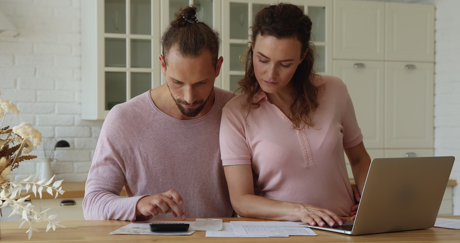 Concentrated young family couple managing household expenditures, calculating utility bills or taxes, paying for services online in e-banking application on computer, planning budget or investing. Royalty-Free Stock Footage #1071353887