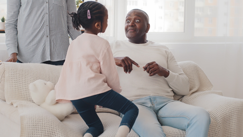 African little schoolgirl child girl talking with elderly man grandfather mature father sitting on couch afro black dad open eyes wide surprised from conversation unrecognizable woman stands near sofa