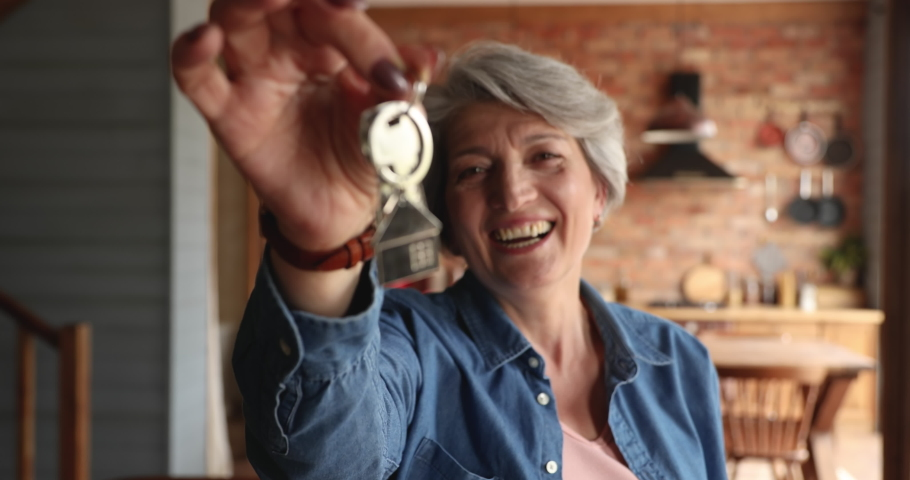 Overjoyed sincere middle aged senior woman holding keys in hands, showing to camera. Happy excited elderly female retired homeowner celebrating purchasing own dwelling, real estate service concept. Royalty-Free Stock Footage #1071403327