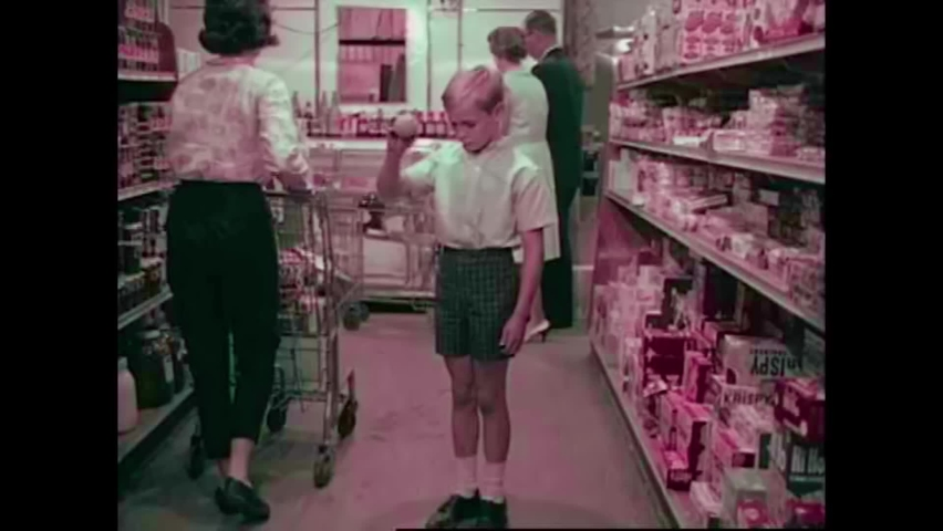 CIRCA 1960s - In a crowded supermarket, a love struck young couple walks down a grocery aisle, but they are arguing by the time their cart is full.