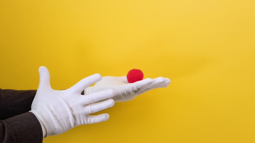 Male magician's hands in white gloves show the trick with a red foam ball. Yellow background. The concept of entertainment and illusions.
