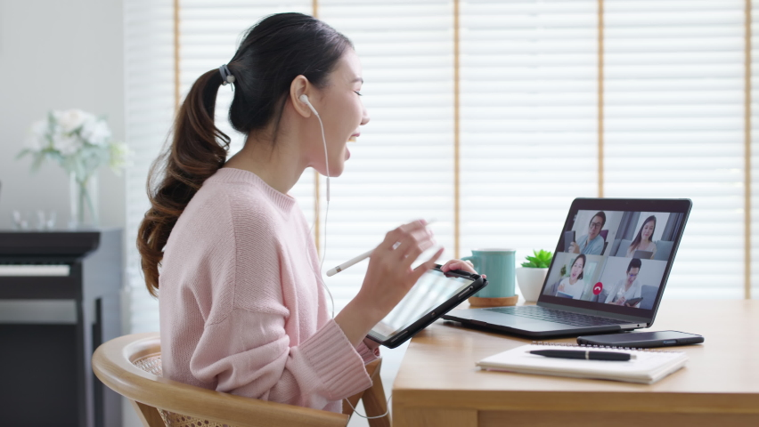 Back view of business woman talking about sale report in video conference. Asian team using laptop and tablet online meeting in video call.Working from home, Working remotely and Social isolation. Royalty-Free Stock Footage #1071513025